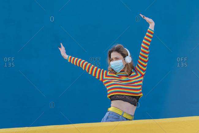 Happy young woman dressed in a colored striped jersey and medical mask on a blue and yellow background listening to music with headphones
