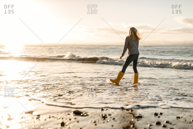 Girl walking with rain boots in the ocean waves at sunset