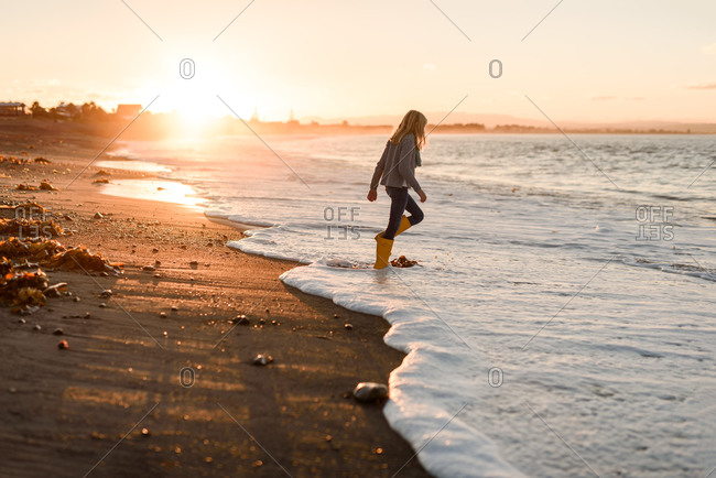 Young teen girl walking with rain boots in the ocean waves at sunset