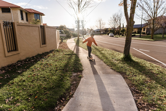 Child riding skateboard on residential sidewalk