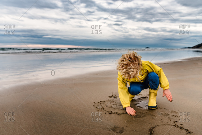 Young boy writing in the wet sand with his fingers