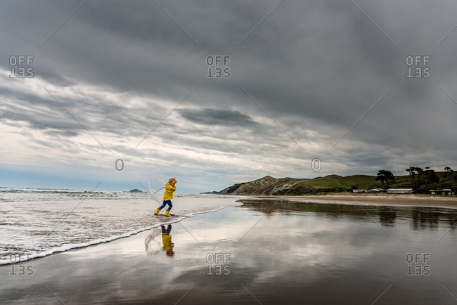 Boy walking on beach with umbrella
