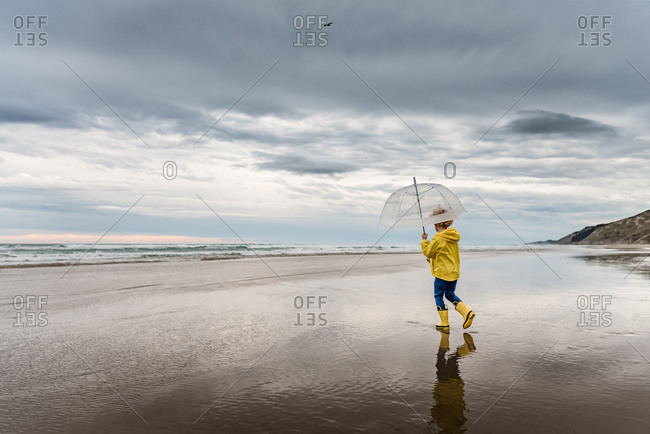 Young boy walking on beach with umbrella