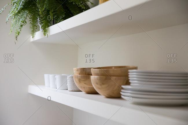 Dishes neatly arranged on white kitchen shelf