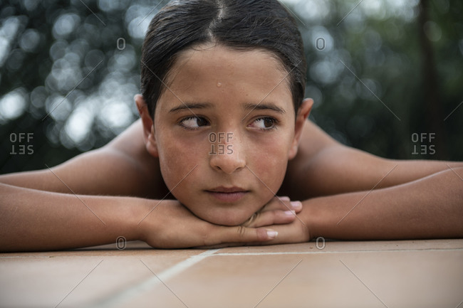 Boy resting on edge of the swimming pool
