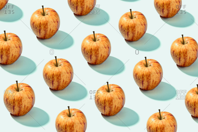 Pattern background of red apples on cyan background. Vibrant colorful pattern