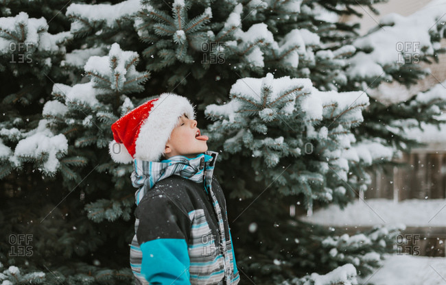Young boy in Santa hat catching snowflakes on tongue on snowy day.