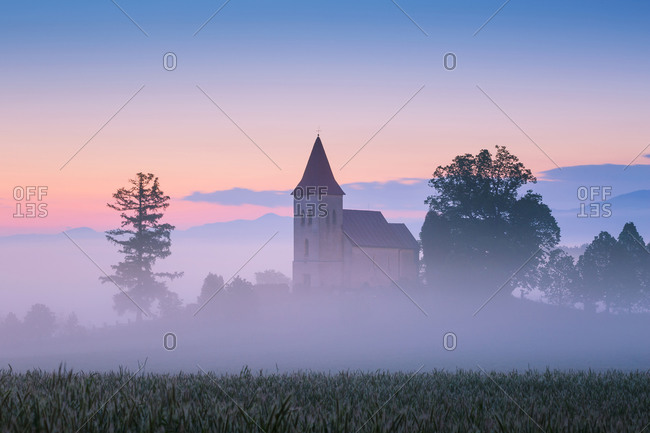 Rural Gothic church in a cemetery on a foggy morning.