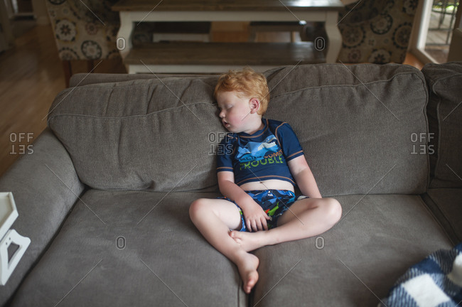 exhausted toddler boy 2-3 years old asleep sitting up on couch at home