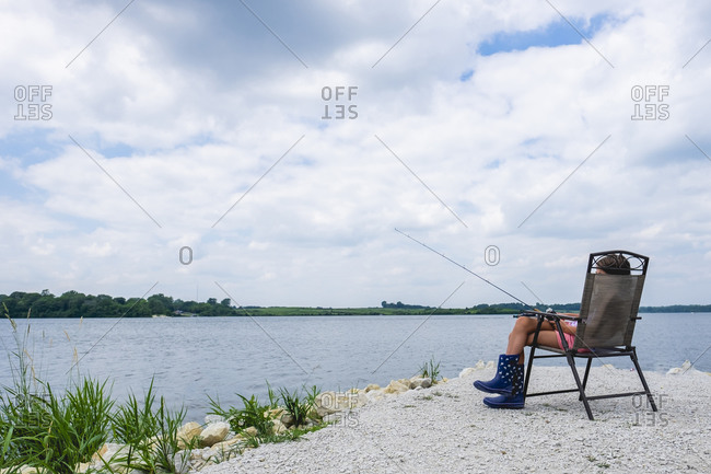 Tween girl 10-12 years old sitting outdoors by water fishing