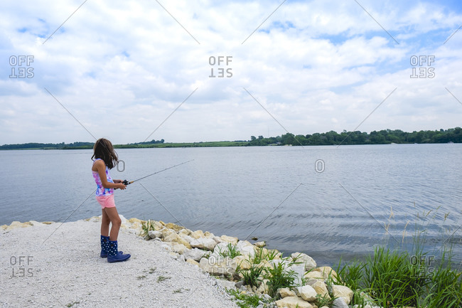 Teen Girl 10-12 years old standing near water fishing on summer day