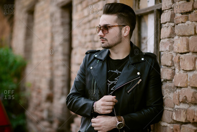 Trendy Man with sunglasses in a jacket standing by a brick wall.