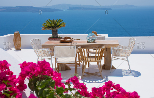 furniture composed by a table and some chairs on a white floral terrace of a house in Santorini Greece where you can enjoy a meal while seeing a romantic seascape to the blue Aegean sea. Hori