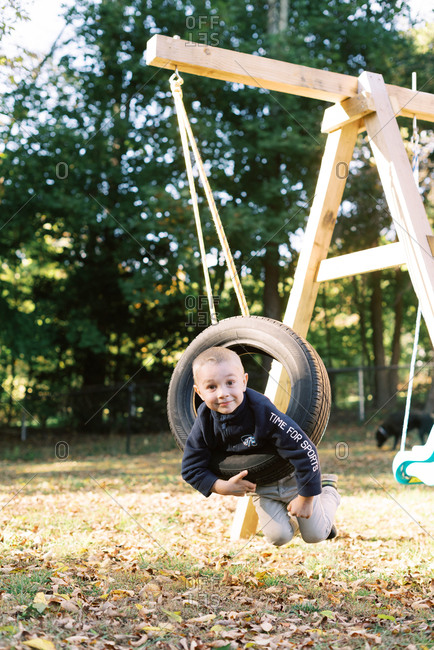 Little boy playing with a tire swing.