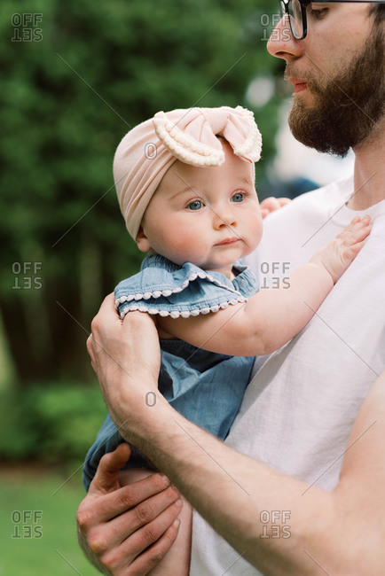 Little baby girl being held by her father.