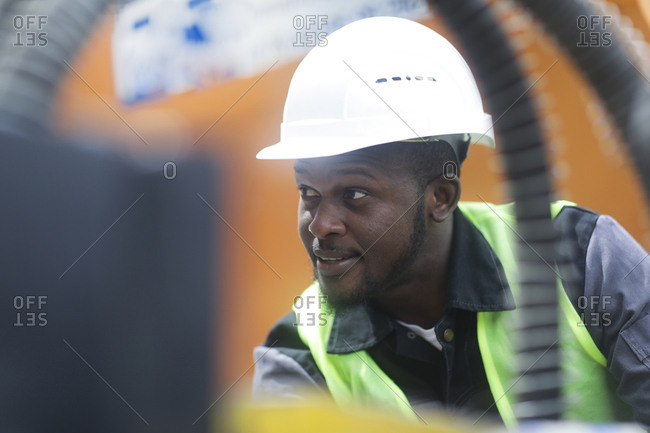 worker young male with helmet outside looking