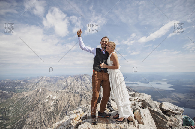 Newlywed bride and groom celebrate on mountain after getting married
