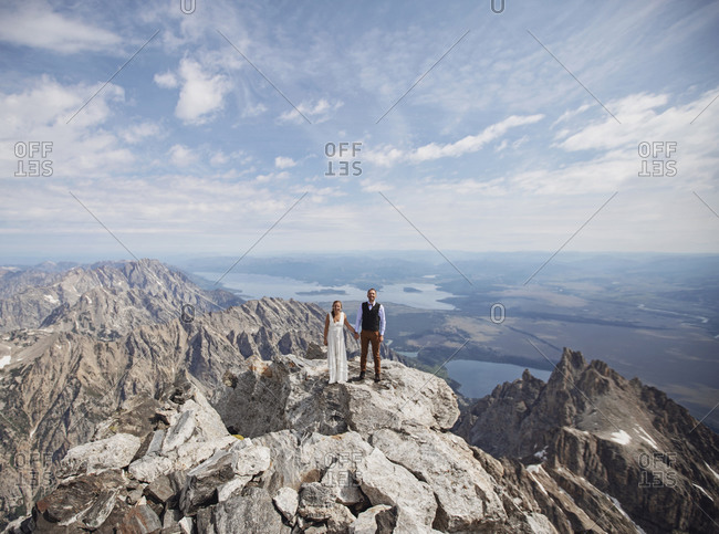 Bride and Groom stand on summit of Grand Teton after getting married.