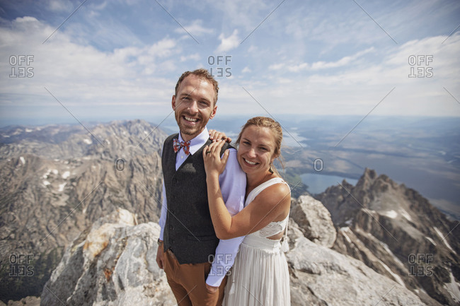 happy Bride and Groom smile on mountaintop after getting married