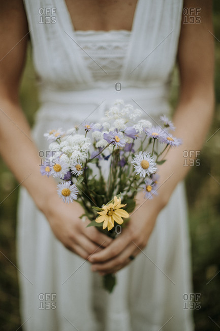 closeup of bride holding wildflower wedding bouquet