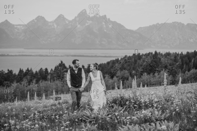 black and white happy smiling bride and groom in field of wildflowers