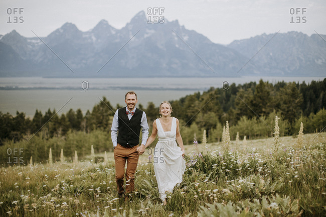 happy smiling newlyweds walk through field of wildflowers in Tetons