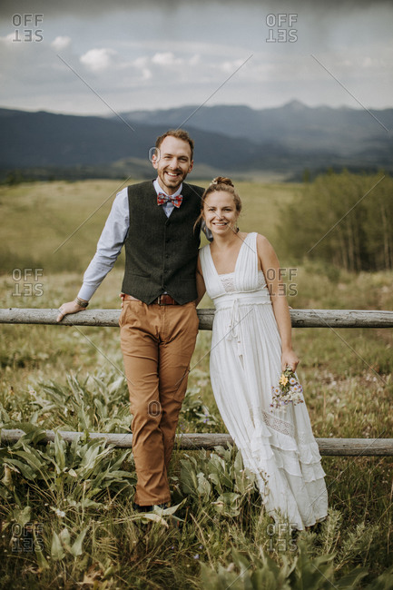 smiling happy bride and groom lean against fence in field in Wyoming