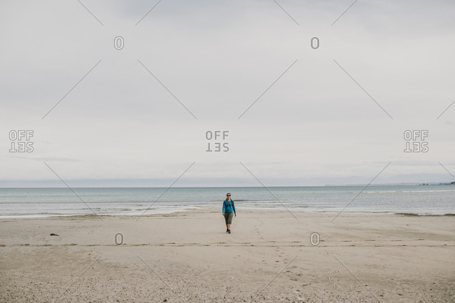female walks alone on beach Abel Tasman National Park New Zealand