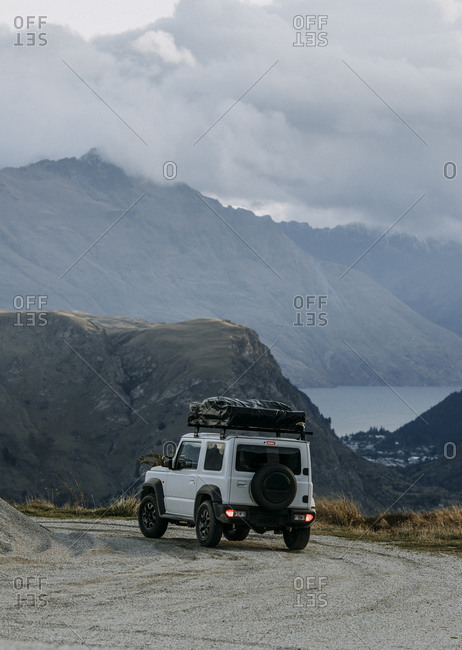 White SUV with rooftop tent on dirt road overlooking Queenstown