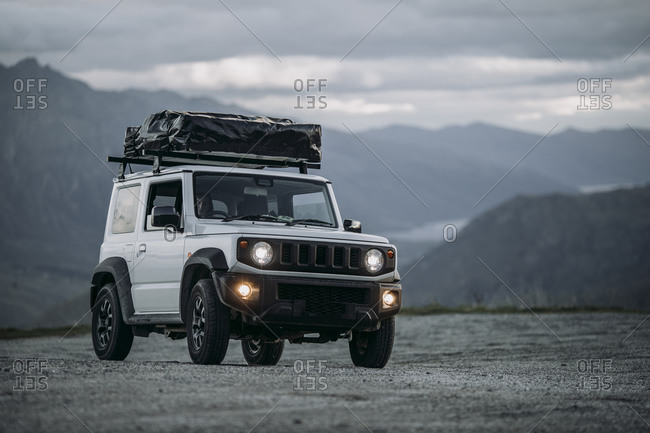 A White off road SUV drives a dirt road in the mountains of New Zealan