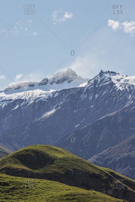 Vibrant green hills sit below wind swept Mount Aspiring, New Zealand