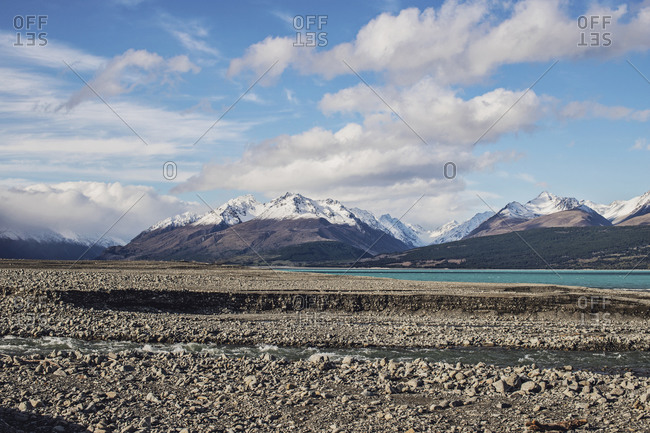 Snowy mountains loom behind turquoise waters of Lake Pukaki, NZ