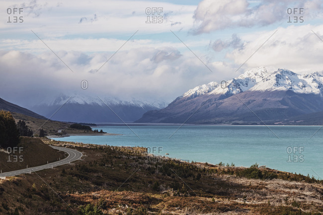 Road to Mount Cook curves into distance next to blue waters of a lake