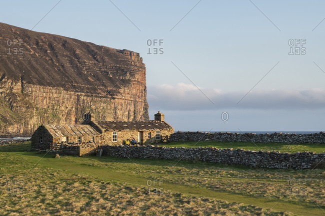 Burnmouth Bothy stone shelter in below dramatic sea cliffs at Rackwick Bay, Hoy, Orkney, Scotland