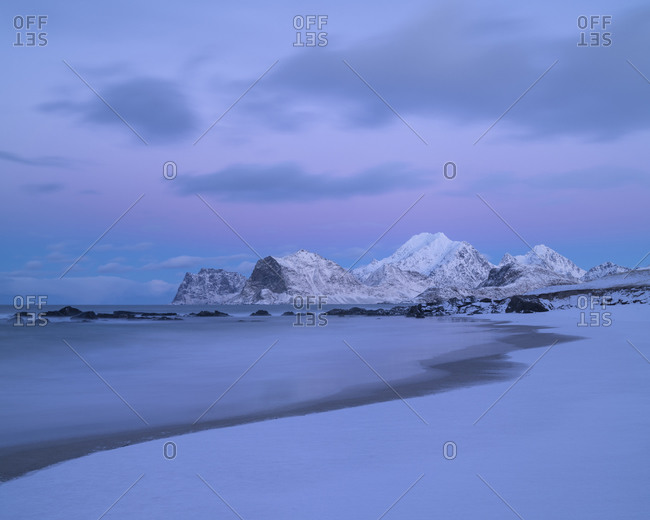 Winter twilight over snow covered Storsandnes beach, Flakstadøy, Lofoten Islands, Norway