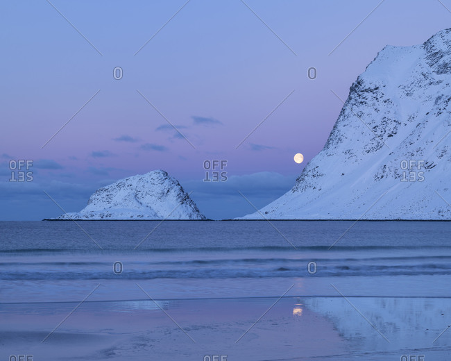 Full moon setting over Vik beach in winter twilight, Vestvågøy, Lofoten Islands, Norway