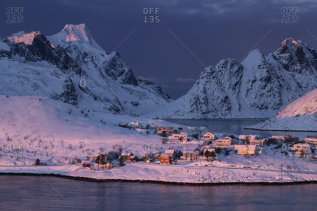 Pink winter light at dawn shines over small coastal village and mountains, Reine, Moskenes√∏y, Lofoten Islands, Norway