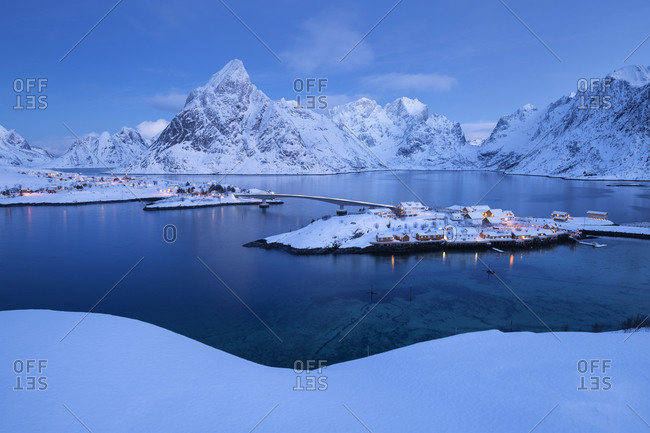 Winter twilight over Sakrisøy and Olstind mountain peak, Moskenesøy, Lofoten Islands, Norway