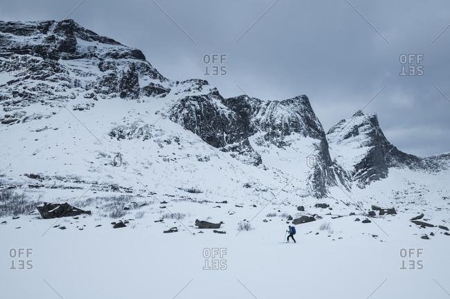 Ski tourer crossing frozen lake, Lofoten Islands, Norway