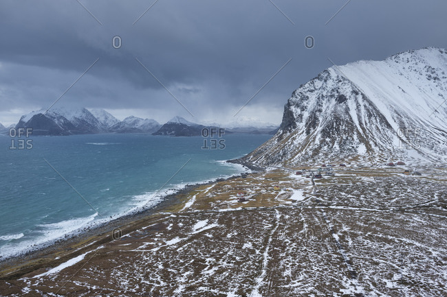Winter view over coastal village of Myrland and surrounding mountain peaks, Flakstad√∏y, Lofoten Islands, Norway