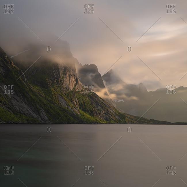 Misty clouds drift over mountain peaks above Fjord landscape, Reine, Moskenesøy, Lofoten Islands, Norway