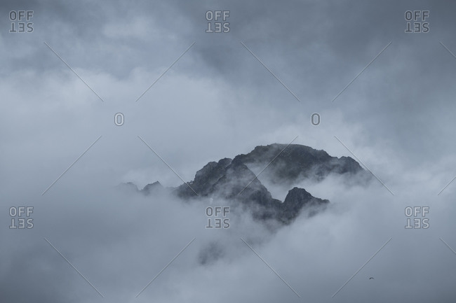 Distant mountain peak emerges from thick clouds, Reine, Moskenesøy, Lofoten Islands, Norway