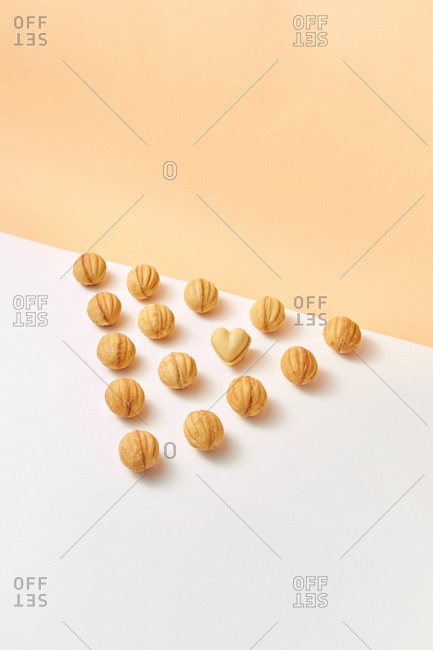 Freshly baked cookies in the shape of walnuts arranged in a triangle on a duotone background