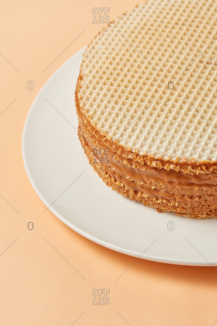 Homemade waffle cake with caramel milk filling on a pastel beige background