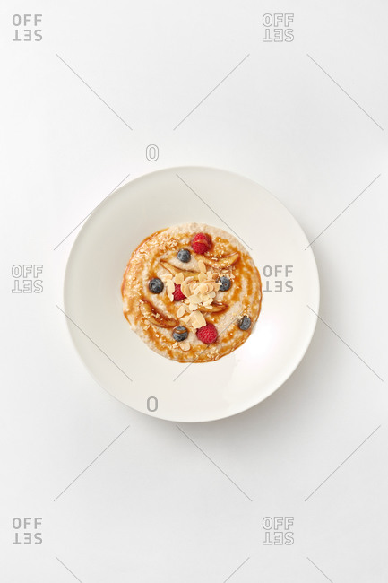 Oatmeal with fresh fruits, berries and almond kernels on a white plate on a light grey background
