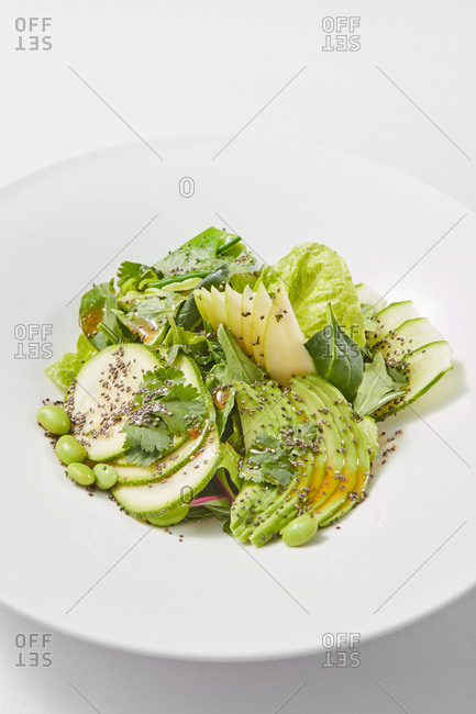 Organic salad with avocado and apples on a ceramic plate