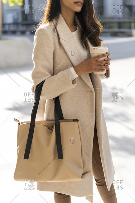 Young woman with takeaway coffee on the go in the city