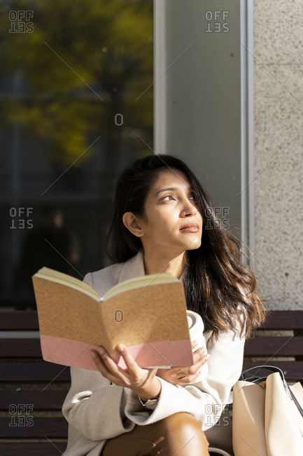 Young woman with book on a bench looking sideways