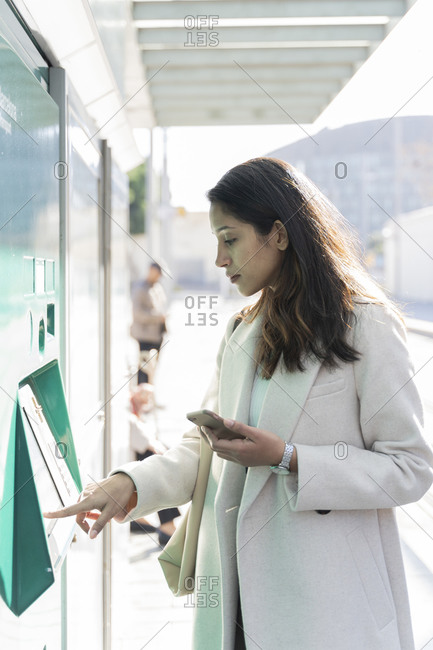 Young woman using ticket machine at tram stop