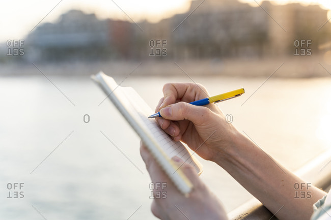 Crop view of young woman writing in notebook at evening twilight